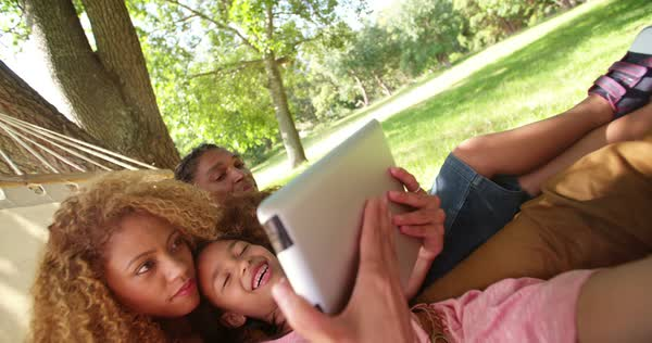 Stunning mother and handsome father spending quality time with their beautiful daughter on a hammock looking at photos on theit tablet on a relaxing summer day at the park. Royalty-free stock video