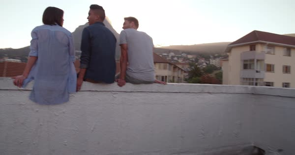 Back view of friends sitting on the parapet of a rooftop watching the sunset all over the city Royalty-free stock video