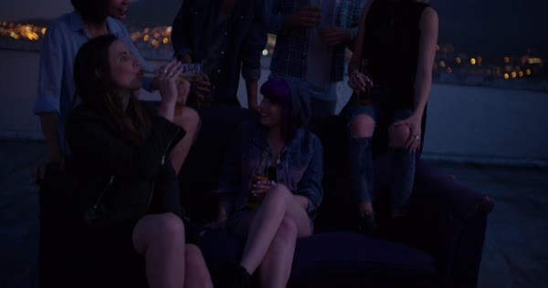 Group of hipster friends enjoying a night rooftop party sitting on a couch with drinks Royalty-free stock video