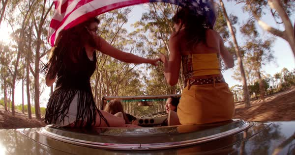 Tilted angle view of group of teenager friends enjoying a road trip in USA and holding an American flag while sitting on the back seat of a vintage convertible car Royalty-free stock video