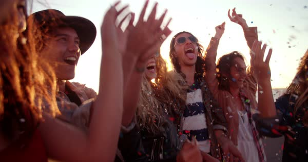 Group of teenager hipster friends partying by blowing and throwing colorful confetti from hands with sunset sun flare Royalty-free stock video