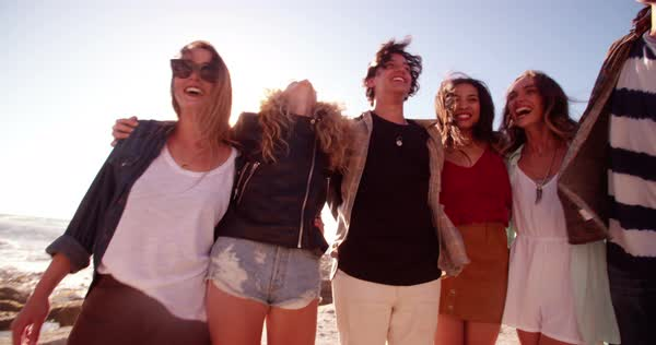 Group of friends in hipster style embracing each other joyfully on a sunny day with backlit Royalty-free stock video