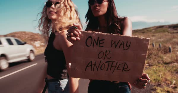 Hipster woman and hipster woman in the daytime stand on side of two lane highway hitchhiking while holding cardboard sign with the One Way or Another written on it and sticking out thumb Royalty-free stock video