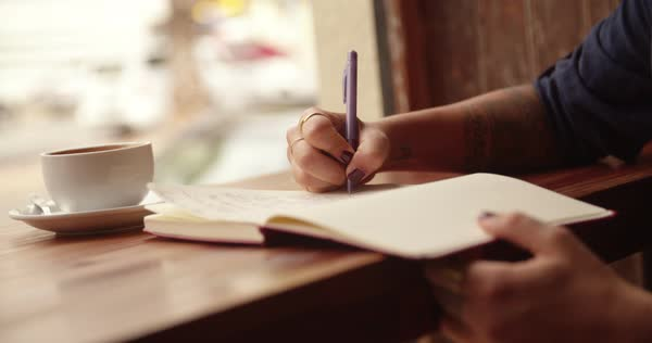 Close-up of a Woman sitting and writing in her journal in busy coffee shop Royalty-free stock video
