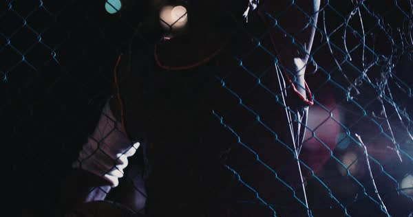 Basketball player resting against court fence, holding ball against hip in the night with lights in background Royalty-free stock video