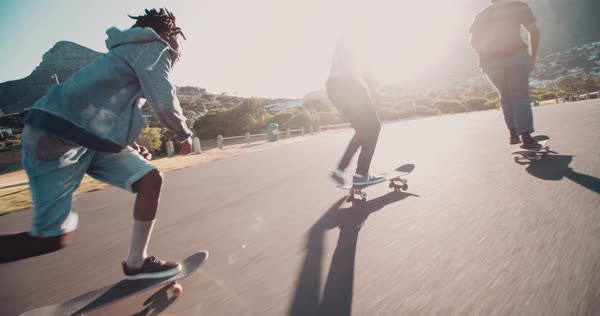 Group of skater friends skateboarding down road at seaside together during sunset Royalty-free stock video