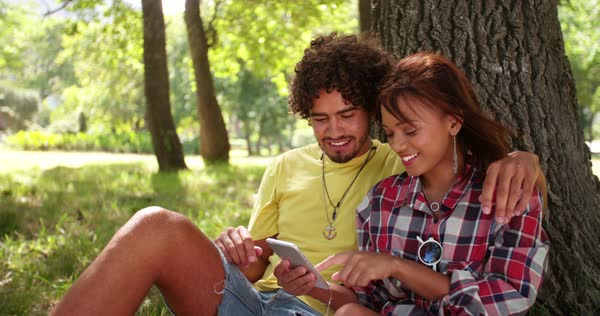 A couple sit closely together, looking, smiling and texing in amusement on smartphone in park. Royalty-free stock video