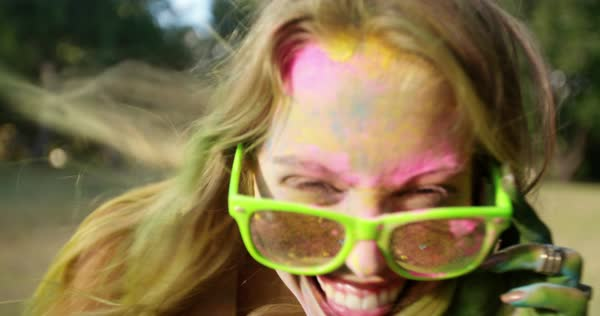 Close-up face shot of Holi powder covered young woman smiling and dancing in a park Royalty-free stock video