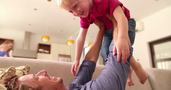 Father and little son play together in the morning on sofa inside a sunlight filled livingroom Royalty-free stock video
