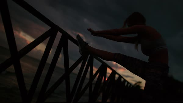 Young woman stretching her legs at dawn preparing for intense workout by the sea. Royalty-free stock video