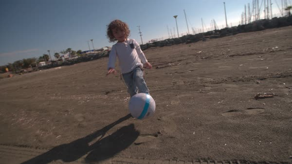 Cute blond curly child playing football on the beach Royalty-free stock video