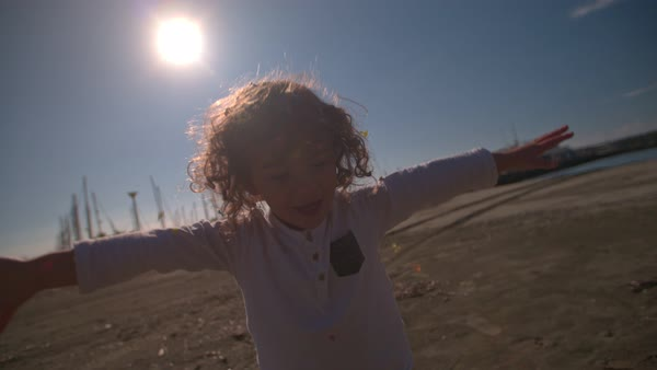 Cheerful young boy throwing confetti at the beach with his arms outstretched  Royalty-free stock video