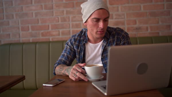 Attractive young man in casual wear and beanie, drinking coffee and going online at modern coffee shop Royalty-free stock video