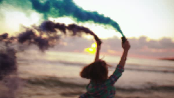 Young woman playing with blue and purple smoke grenades on seaside at sunset Royalty-free stock video