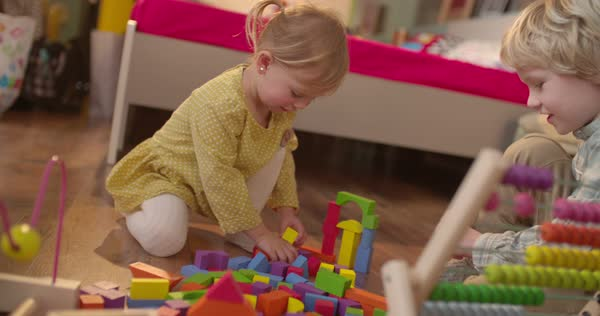 Young preschooler girl and her school age brother playing with toys on the floor Royalty-free stock video