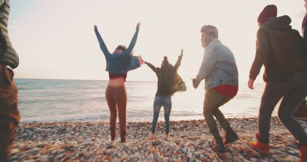 Group of young hipster friends running, jumping and enjoying a day at the beach Royalty-free stock video