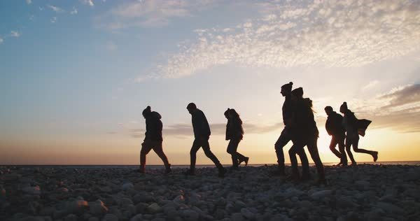 Group of hipster people walking together on a beach with pebbles in winter at sunset Royalty-free stock video