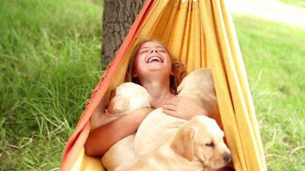 Laughing girl swinging in hammock with puppies in slow motion Royalty-free stock video