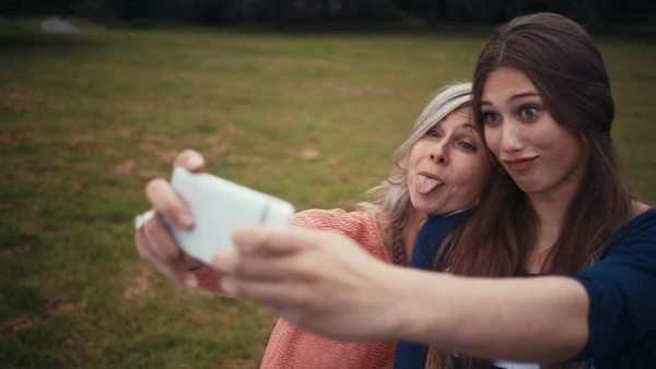 Mother and daughter pose together for a selfie with their smart phone Royalty-free stock video