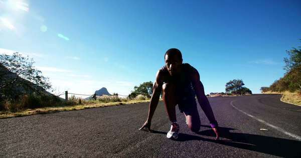 Runner tying his shoelaces, then in a starting ready position. runs out of the shot in slow motion Royalty-free stock video