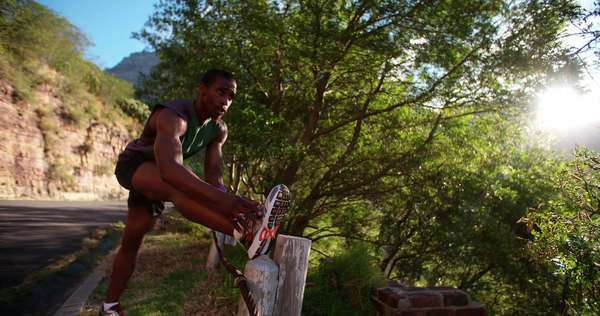 Focused athlete massaging his tired muscles on the roadside during an outdoor exercise session in slow motion Royalty-free stock video