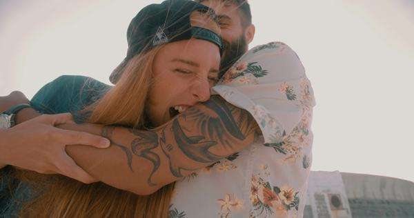 Playful hipster girl pretending to take big bite out of her boyfriend's tattooed arm while hanging out at the beach Royalty-free stock video