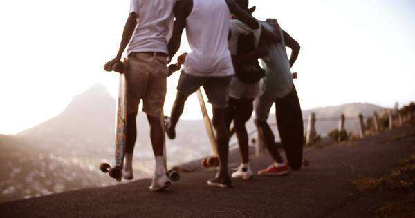 Rear view shot of a group of American teen friends dancing happily together with their long boards in slow motion Royalty-free stock video