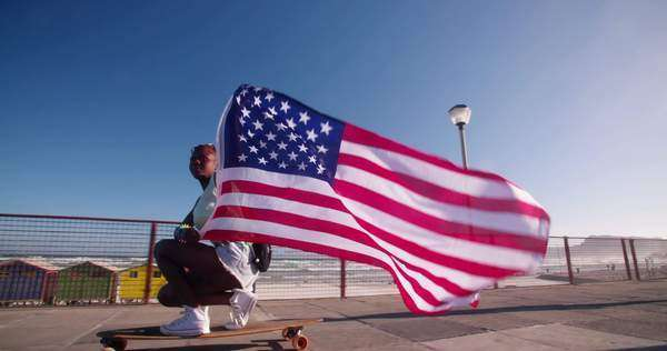 Teenage skater flying an American flag past the camera Royalty-free stock video