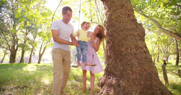 Happy parents swinging their cute laughing toddler under a tree in a park in slow motion Royalty-free stock video