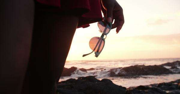 Cropped Close-up of a hipster's hand holding retro sunglasses at the beach with sun flare Royalty-free stock video