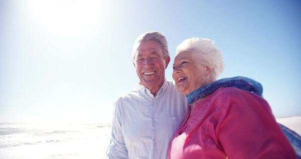 Happy senior retired couple walking together joyfully on the beach in slow motion Royalty-free stock video