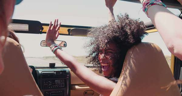 Girl laughing in a vehicle with friends on a summer road trip vacation in slow motion Royalty-free stock video