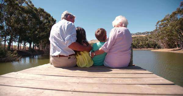 Rearview of grandparents sitting with their grandchildren on a lakeside jetty Royalty-free stock video