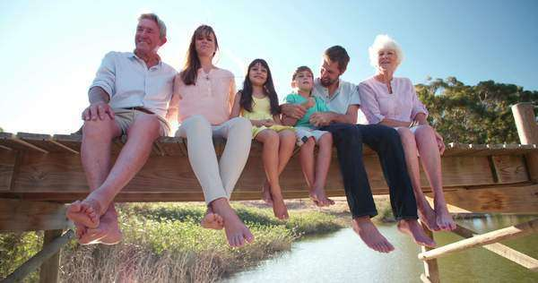 Three generation family outdoors on a summer vacation relaxing together on a jetty Royalty-free stock video
