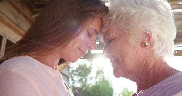 special moment between a senior woman and her loving adult daughter standing close together outdoors with sun flare, panning in slow motion Royalty-free stock video