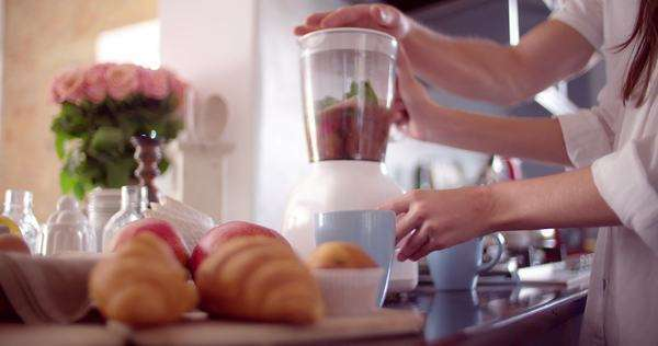 Man juicing a breakfast in his kitchen for his girlfriend and himself Royalty-free stock video