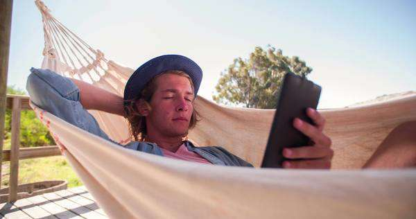 Guy on holiday relaxing in a hammock reading an eBook outdoors, panning in slow motion Royalty-free stock video