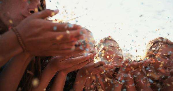 Group of happy teens blowing colorful confetti from their hands together with sun flare outdoors, panning in slow motion Royalty-free stock video