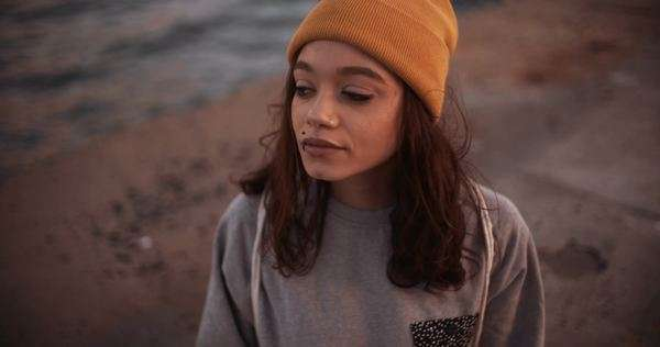 High angle view of a grungy teen girl wearing a yellow beanie and sitting alone on a pavement Royalty-free stock video