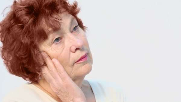 Portrait of senior woman supports her head by hand, closeup view isolated on white Royalty-free stock video