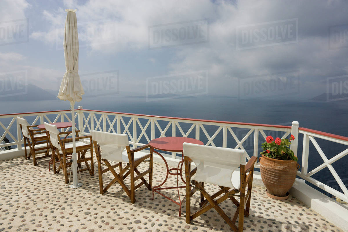 Greece, Santorini, Thira, Oia. Patio Tables And Chairs On Pebbled Deck  Overlooking Misty Sea.