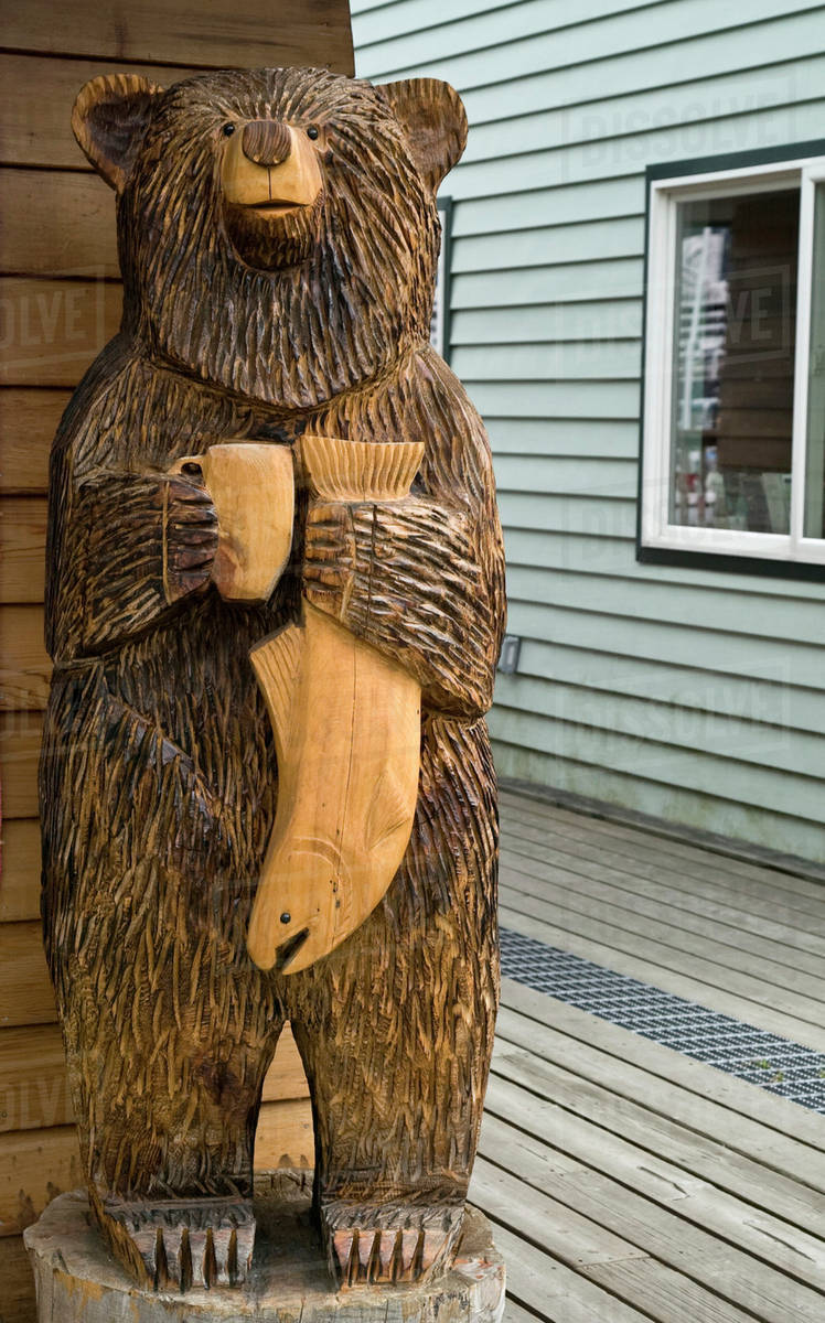 Usa Alaska Seward Carved Wooden Bear Statue Holding A Fish And A Cup Of Coffee Stock Photo