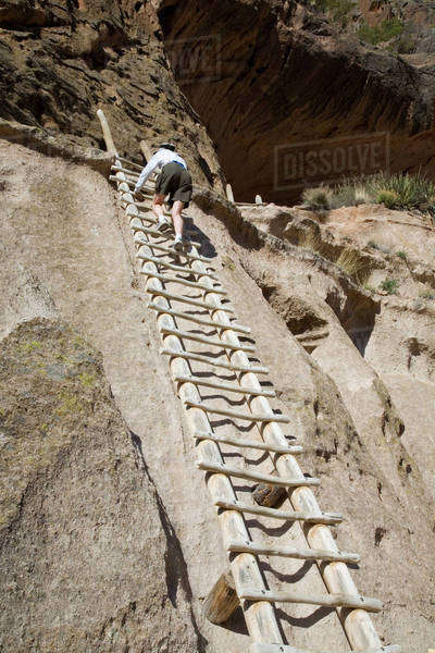 NM, New Mexico, Bandelier National Monument, in Frijoles Canyon, home of Ancestral Pueblo people, canyon wall is a soft rock called tuff, ladders to Alcove House, a 140 foot climb Royalty-free stock photo
