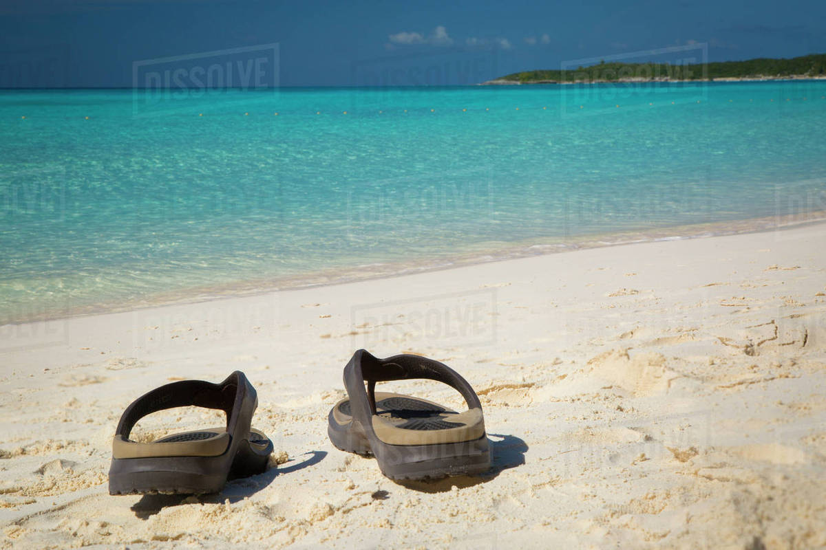 b05f4c408 Flip flops on a sandy beach with turquoise water beyond
