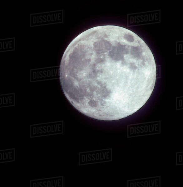 A bright full moon in a black night sky. Rights-managed stock photo