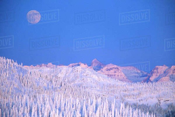 Full moon rising above Glacier National Park Peaks from summit of Big Mountain in winter in Whitefish, Montana, USA. Rights-managed stock photo