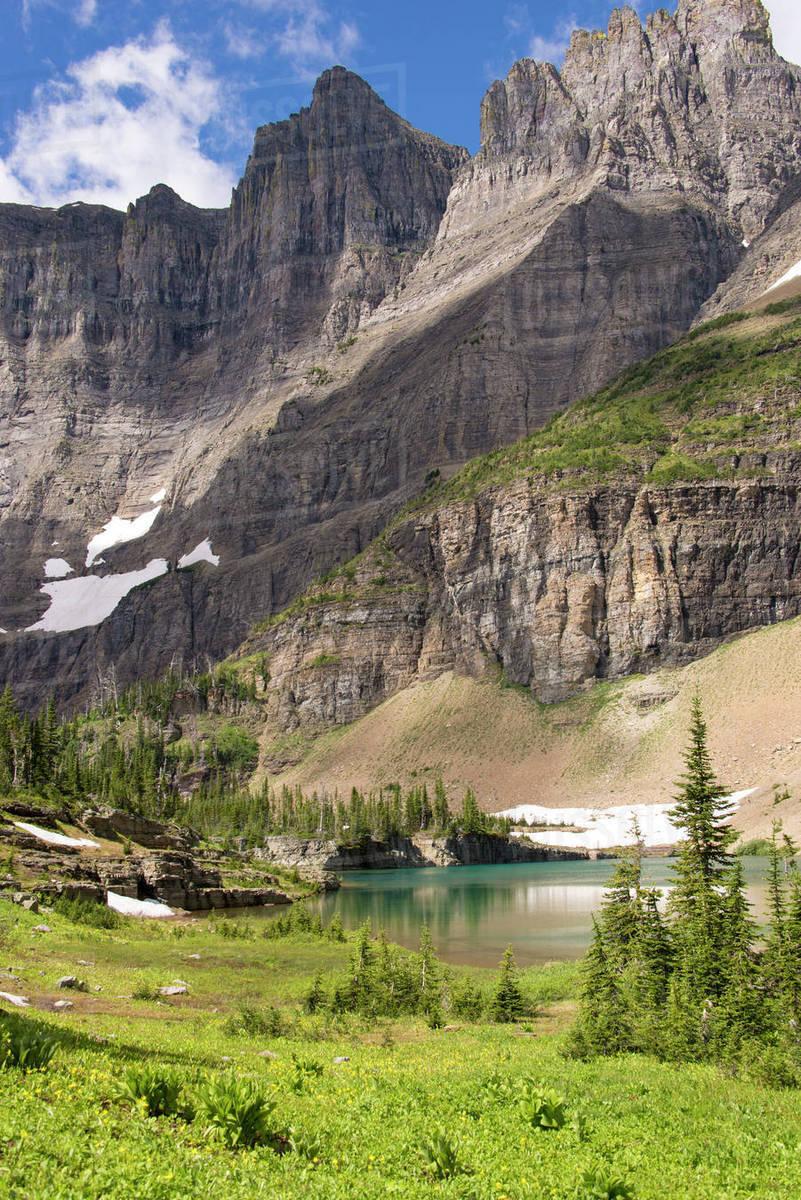 Glacier National Park  Ptarmigan Wall  Alpine lake along Iceberg Lake trail  stock photo