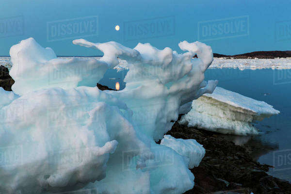 Canada, Nunavut, Territory, Moonrise framed in arch of melting iceberg along Frozen Strait in northern Hudson Bay near Arctic Circle Royalty-free stock photo