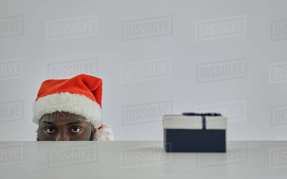 The african man in the santa hat watching from the table with a gift Royalty-free stock photo