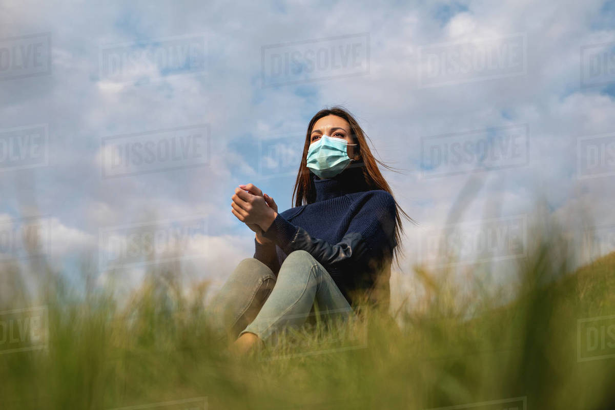 The beautiful woman in medical mask sitting on the green grass Royalty-free stock photo